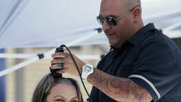 Chloe Herrera gets her hair shaved Tuesday, April 18, 2017 on the UTSA campus by her husband, Ted, during a fundraiser sponsored by Honors College students at UTSA for the St. Baldrick's Foundaiton, which supports cancer research. Herrera was the top fundraiser for the event.