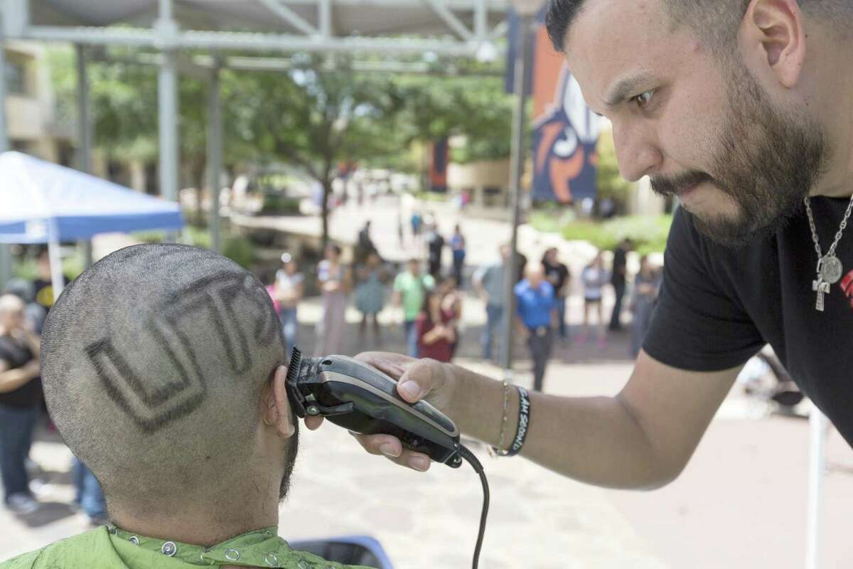 """Jay Reyna of Pitts Barber Shop shaves """"UTSA"""" into Alex Briones hair Tuesday, April 18, 2017 on the UTSA campus during a fundraiser sponsored by Honors College students at UTSA for the St. Baldrick's Foundaiton, which supports cancer research."""