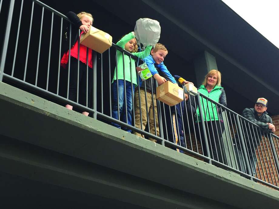 With two parent volunteers, at right, watching, Kate Cadagin, Mackenzye Engelmann andTyler Ferguson prepare for the egg drop. Photo: Julia Biggs • Intelligencer