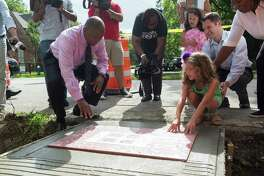 Houston Mayor Sylvester Turner, left, and Sophie Blitz finish the last piece of sidewalk repair near Sophie's home at the Houston Heights. Sophie wrote Mayor Turner to ask for sidewalk repairs so she could safely walk and ride her bike to Harvard Elementary.   ( Marie D. De Jesus / Houston Chronicle )
