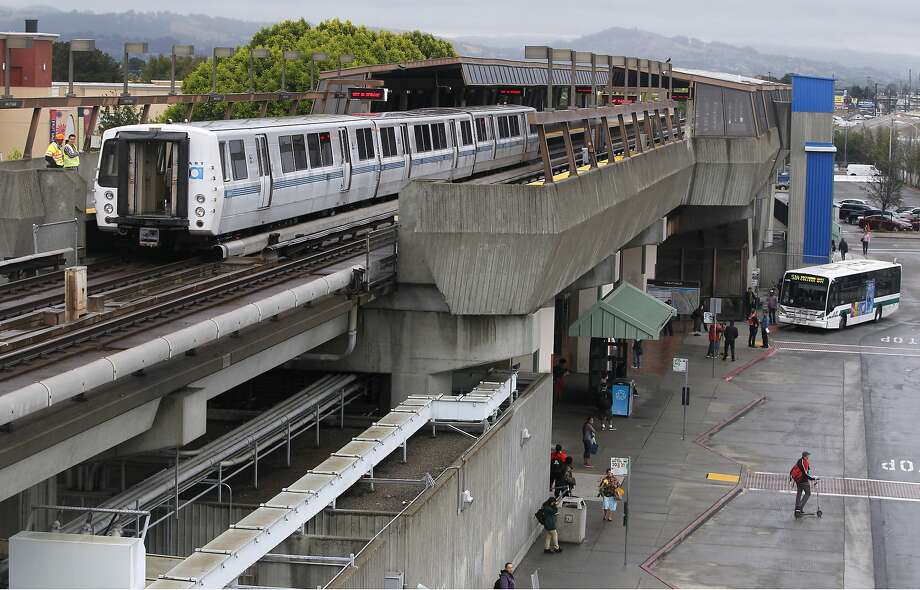 BART employees (left) stand outside a damaged 3-car train at the Fruitvale station as stranded commuters seek alternate transportation in Oakland, Calif. on Thursday, July 9, 2015 after an early morning fire below the train between the Coliseum and Fruitvale stations disrupted the morning commute. At least three passengers aboard the train were transported to hospitals. Photo: Paul Chinn, The Chronicle