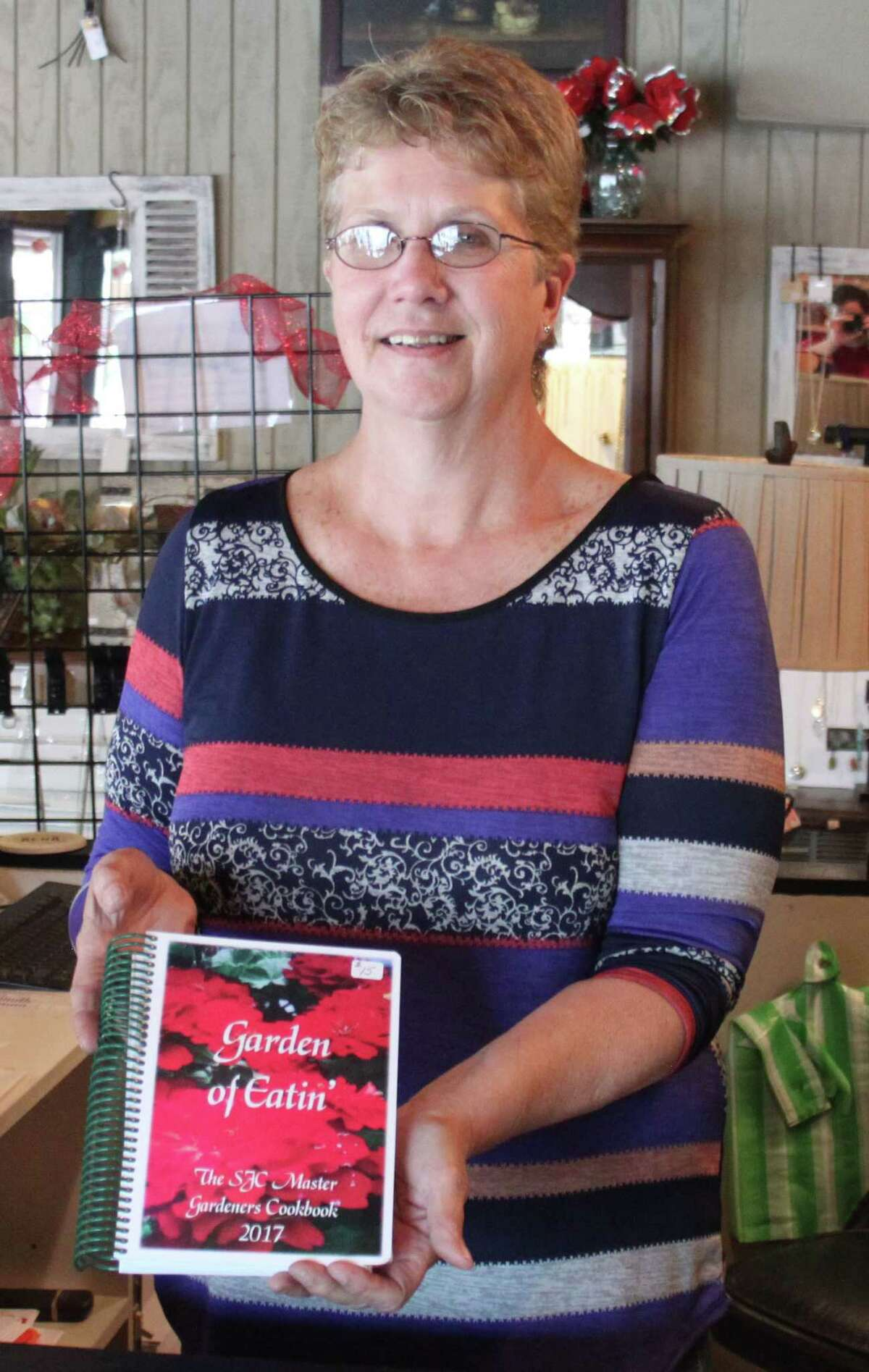 Barbara Shelton presents a copy of the Garden of Eatin' cookbook. The cookbook is available at various vendors around Coldspring and Shepherd and the sales go to helping the San Jacinto County Master Gardeners fund their events and activities.