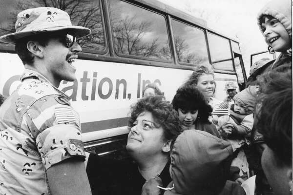 Sgt. Laurance Robert Flemming Jr. is greeted with a mix of adoration and happiness from his family - wife, Lauri; Amanda, 4, far right, and Robert, 1, bottom with back to camera. May 1991