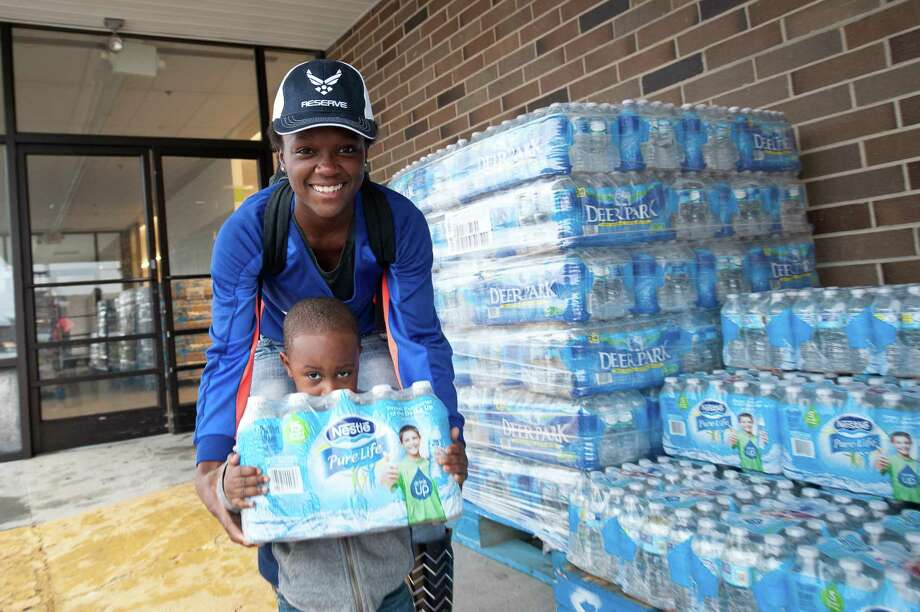 Nearly 10 million bottles of Nestle Waters North America-produced water has been distributed by Americares to areas affected by natural disaster and public health crises. Here, two local residents distribute water in Columbia, S.C., after flooding in October 2015. Photo: CMichaelBergen.com /Americares