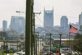 Utility polls line the street in downtown Nashville, Tenn., with AT&T�s building in the distance, March 27, 2017. Google Fiber struggled to gain access to utility poles in Nashville. AT&T owns many of the poles. AT&T has painted itself as an underdog that needs to merge with Time Warner to compete with powerful cable companies, but its actions to hamper local competitors in several cities and states sends a different message. (Kyle Dean Reinford/The New York Times)