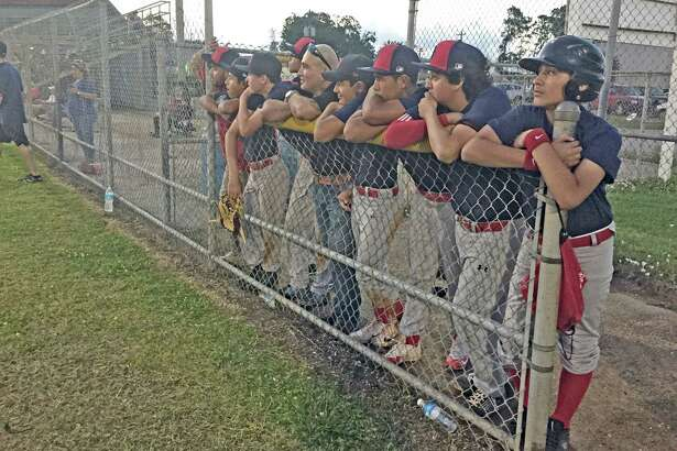Pasadena Pony League players watching their team play are joined by Pasadena City Councilman Sammy Casados, who criticized the city for turning the field lights off on the team a few days earlier.
