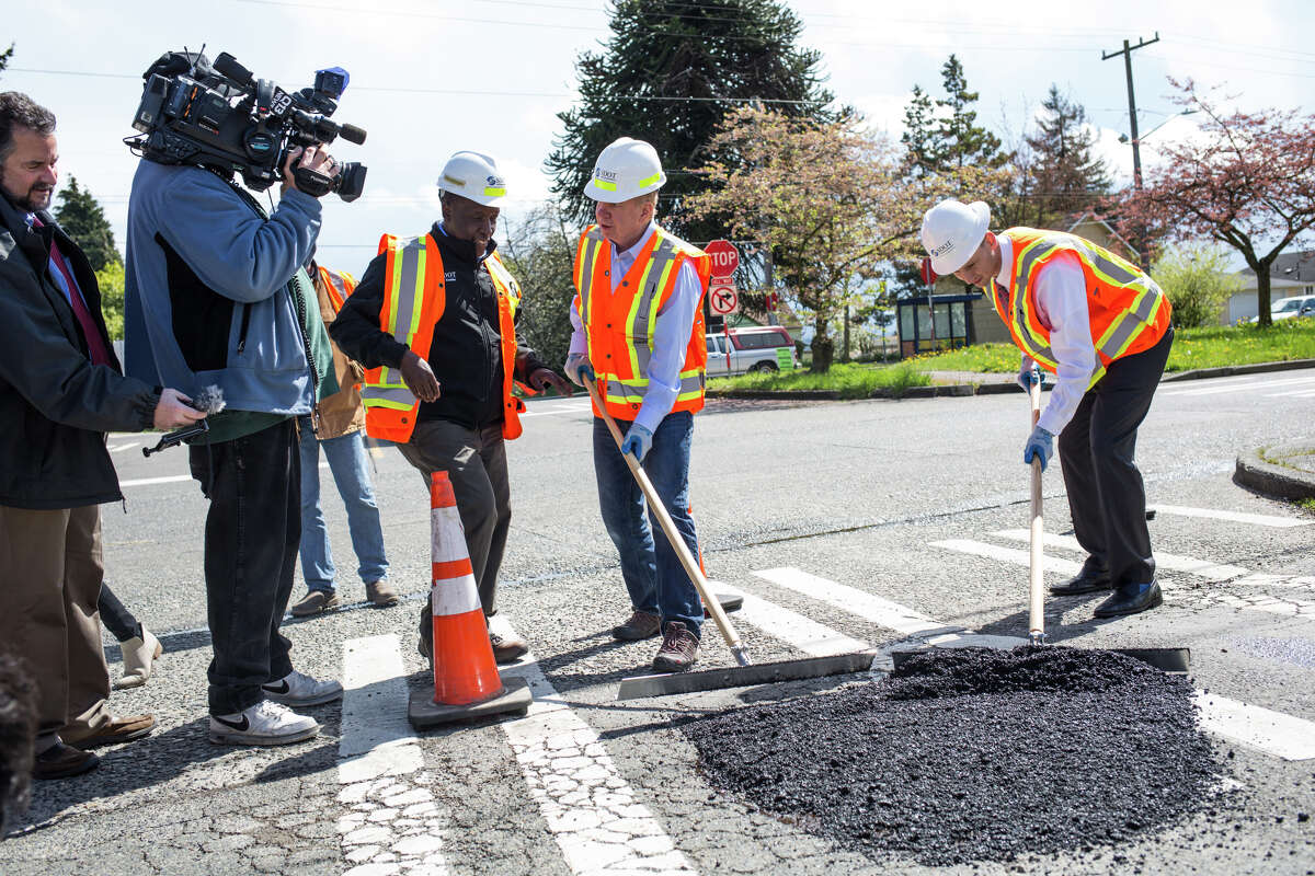 Seattle Mayor Ed Murray and SDOT director Scott Kubly try their hand at filling in potholes at Beacon Avenue South and South Orcas Street on Wednesday, April 19, 2017.