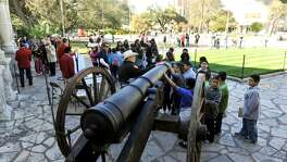 Children look over a replica of the 18-pound cannon fired in response to Gen. Santa Anna's demand for surrender at the Alamo.