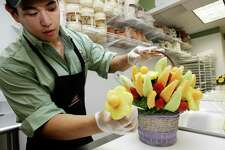 A worker in Mamaroneck, N.Y., demonstrates how to create a holiday centerpiece using fruits for Edible Arrangements.