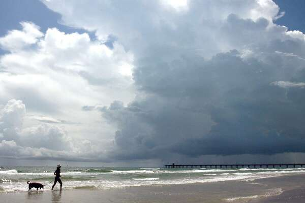 A woman walks her dog along the beach near Bob Hall Prier in Corpus Christi in 2009. A resident schools outsiders on how to refer to his town.