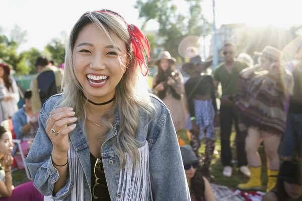 Portrait laughing young woman at summer music festival campsite