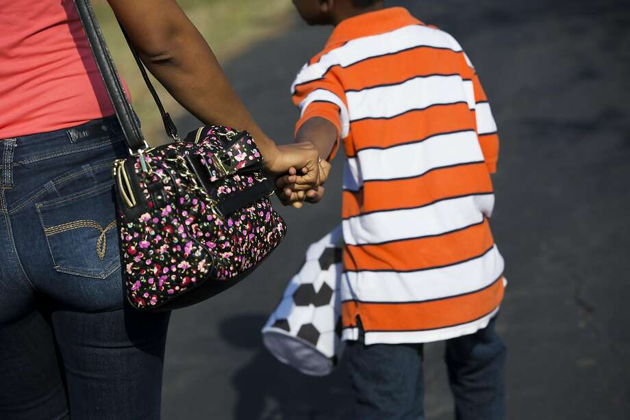 Zecole Thomas and son Ezekiel, 7, cross the road to go to the park in Cary, N.C. Photo: Eamon Queeney, Special To The Chronicle