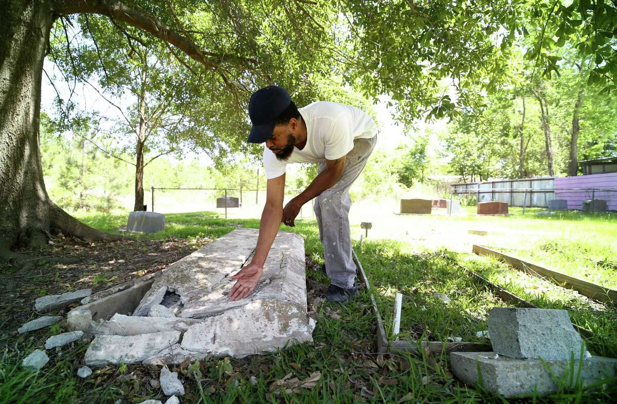 Rod Barnaba takes a close look at the damage on a gravestone after someone drove through part of the historical Barrett Station Evergreen Cemetery Monday, April 24, 2017, in Barrett, Texas.