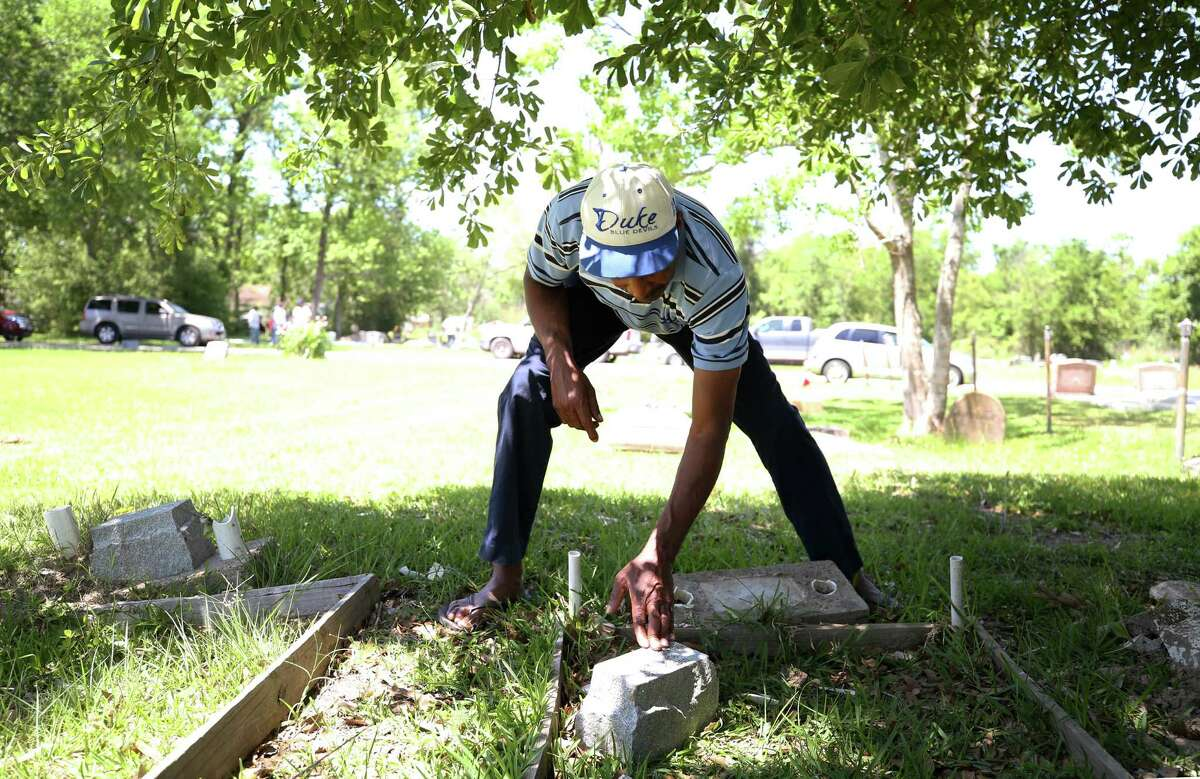 Rennie Matthews looks at tombstone that was damaged by a person who drove through the Barrett Station Evergreen Cemetery Monday, April 24, 2017, in Barrett, Texas.