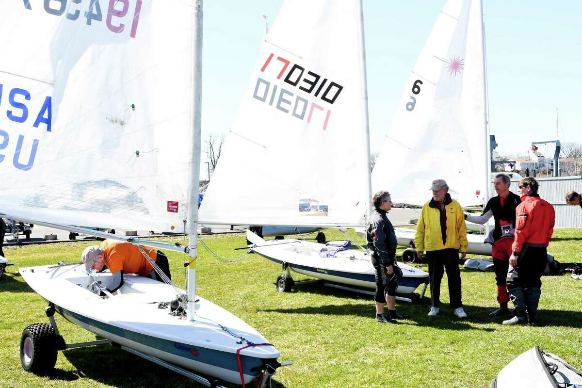 Racing sailboat designer Bruce Kirby talks with some competitors before a recent regatta of his Laser series boats at the Cedar Point Yacht Club in Westport.