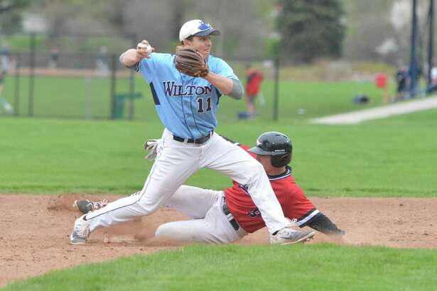 Wilton's Collin Kahal, left, makes the out at second base on Fairfield Warde's Zach McKay on Monday at Wilton High School. Wilton won 5-1.