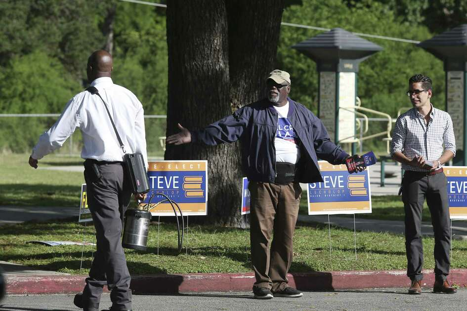 Campaign workers C.J. Littlefield, center, and Mohammad Rasool push for their candidate as they work the early voting site at Lions Field on Broadway on April 24.