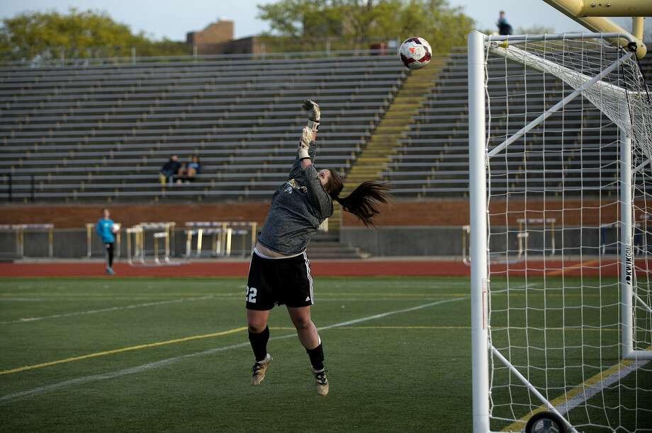 Bay City Western's goalie Molly Mantei jumps to deflect a shot on the goal in the first half of the girls soccer game Monday evening against Midland High. Photo: Brittney Lohmiller/Midland Daily News/Brittney Lohmiller