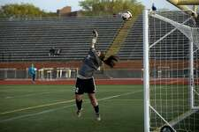 Bay City Western's goalie Molly Mantei jumps to deflect a shot on the goal in the first half of the girls soccer game Monday evening against Midland High.