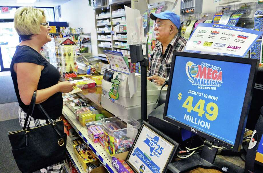 Debbie Penesso of East Greenbush buys a ticket for the $449 million Mega Millions jackpot from Coulson's News Center owner Fershid Hushmendy at Newton Plaza Tuesday July 5, 2016 in Colonie, NY.  (John Carl D'Annibale / Times Union) Photo: John Carl D'Annibale / 20037225A