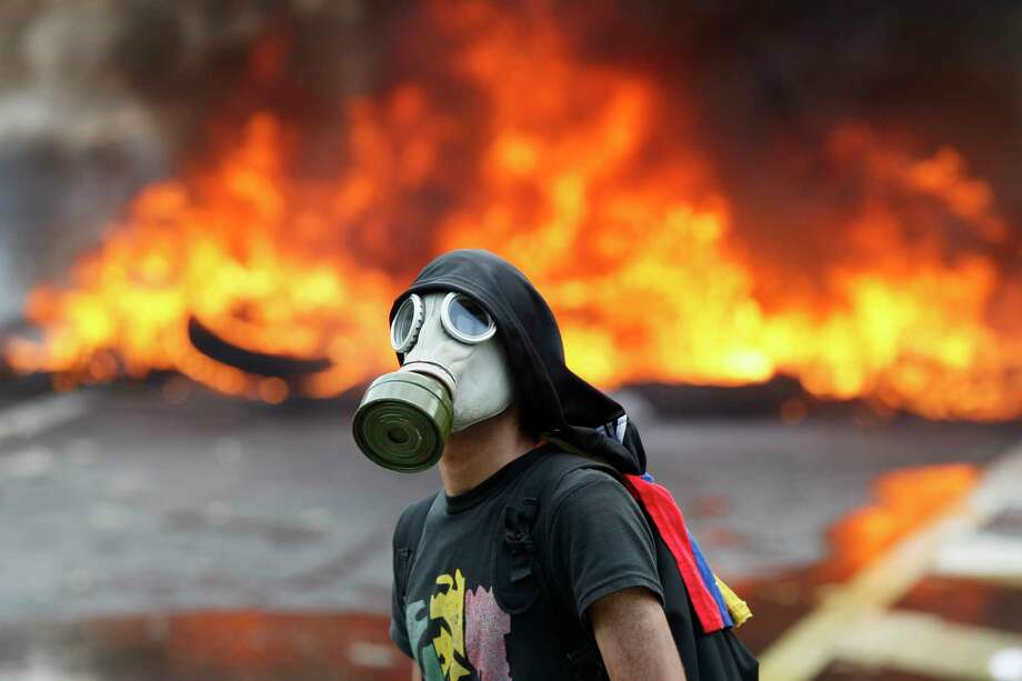 A protester stands in front of a burning barricade Monday on a highway in Caracas, Venezuela. Thousands shut down the city's main highway. Photo: Ariana Cubillos, STF / Copyright 2017 The Associated Press. All rights reserved.