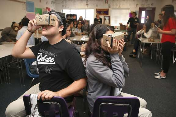Eleventh grade students Eduardo Venegas (left), 17, and Valeria Ochoa (right), 16,  at Aspire Public Schools use Google Cardboard to view virtual reality images that Google has created of sites related to Alexander Hamilton on Monday, April 24, 2017, in Oakland, Calif.