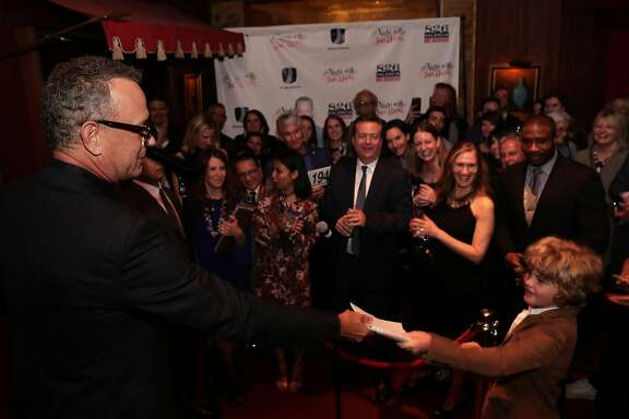 Special guest Tom Hanks gives his copy to 11-year-old Oliver Yeaman, of San Francisco after reading from his new book  Uncommon Type: Some Stories, during a fundraiser to benefit  826 Valencia and ScholarMatch, at Bimbo's 365 Club in San Francisco, Calif., on Monday April 24, 2017.