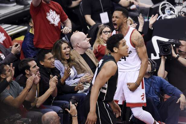Toronto Raptors guard Norman Powell (24) reacts after drawing a foul while making a basket as Milwaukee Bucks guard Malcolm Brogdon (13) looks on during the first half of game five of an NBA first-round playoff series basketball game in Toronto on Monday, April 24, 2017. (Nathan Denette/The Canadian Press via AP)