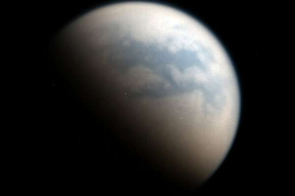 This shot merges red and near-infrared light — which can pierce Titan's thick atmosphere — from Cassini's camera sensor, revealing the partly-lit surface of Titan.  The blue-colored regions are dark material that researchers believe are dry seabeds.