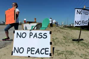 Buffy Dievel, of High Island, holds a protest sign at Rollover Pass on the Bolivar Peninsula on Monday afternoon.  Photo taken Monday 4/24/17 Ryan Pelham/The Enterprise
