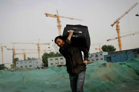 A migrant worker carries his luggage walks past the worker's living squatters on a buildings contraction site in Beijing, Monday, April 17, 2017. China's economic recovery is gaining momentum, with growth ticking up to a 6.9 percent annual pace in the first three months of the year, lifted by government stimulus and a property boom. (AP Photo/Andy Wong)