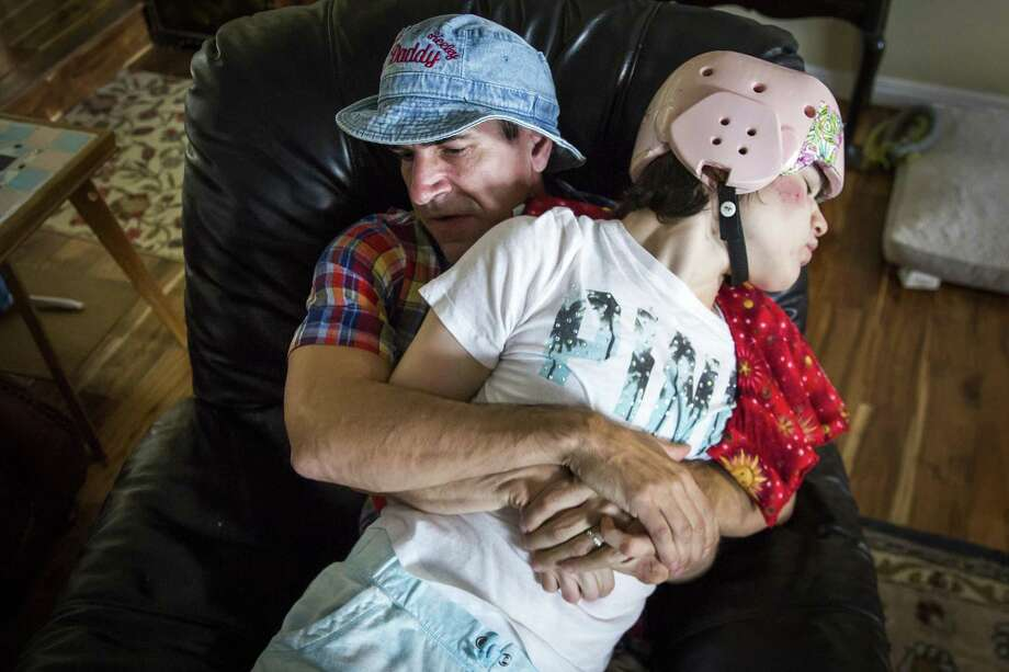 Mark Zartler restrains his daughter to keep her from hitting herself as he rocks with her in a chair after giving her a marijuana vapor treatment  March 18 in Richardson, Texas. Within minutes, Kara was calm. Zartler testified Monday in Austin in favor of House Bill 2200, which would offer a criminal defense to patients who use medical marijuana in Texas. (Smiley N. Pool/Dallas Morning News/TNS) Photo: Smiley N. Pool /TNS / Dallas Morning News