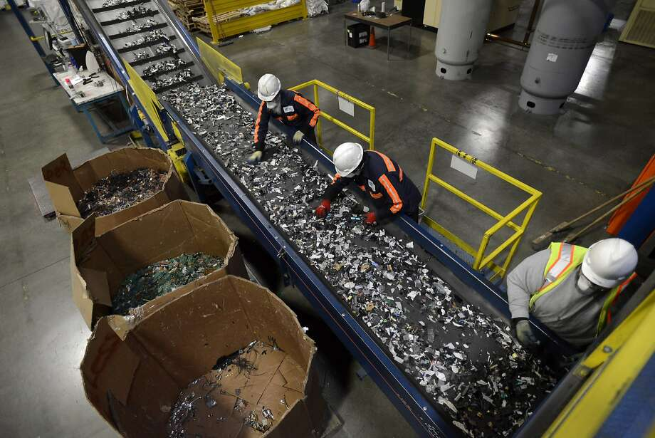 Employees sort through crushed electronic components for recyclable electronic materials at a Sims Recycling Ltd. facility in Roseville, California, U.S., on Friday, Dec. 21 2012. Sims receives much if its material from Green Citizen, a company that collects and disposes old electronics in the San Francisco Bay area. The pieces are put through shredders and broken-down materials are then sold to companies seeking aluminum, plastic, glass or other recycled material. Photographer: David Paul Morris/Bloomberg Photo: David Paul Morris, Bloomberg
