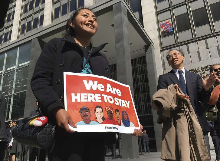 Erica Leyva with the Services, Immigrant Rights and Education Network of San Jose, Calif., carries a sign outside a courthouse where a federal judge heard arguments in the first lawsuit challenging President Donald Trump's executive order to withhold funding from communities that limit cooperation with immigration authorities Friday, April 14, 2017, in San Francisco. An attorney for the U.S. Department of Justice said the executive order withholding funds from sanctuary cities applies to a small pot of grant money, not hundreds of millions of dollars as claimed in lawsuits in California. (AP Photo/Haven Daley)