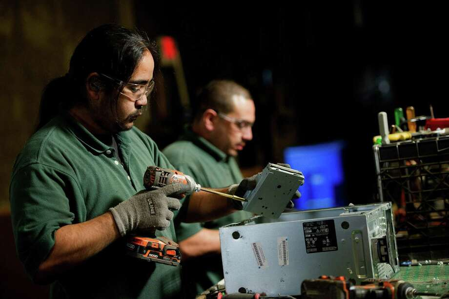 Employees at a Green Citizen recycling facility in Burlingame, California, take apart used electronics to remove valuable materials from inside them. Austin-based Urban Mining Company wants to invest $25 million into San Marcos to build a 100,000-square-foot recycling and manufacturing facility for rare earth metal magnets. Photo: David Paul Morris /Bloomberg / © 2012 Bloomberg Finance LP