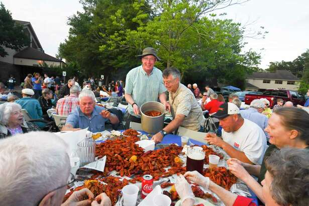 Mark Warpmacker, center left, and Kevin Hughes, center right, had the big job of passing out the thousands of boiled crawfish during the Kinsmen Lutheran Church's crawfish boil and festival Saturday.