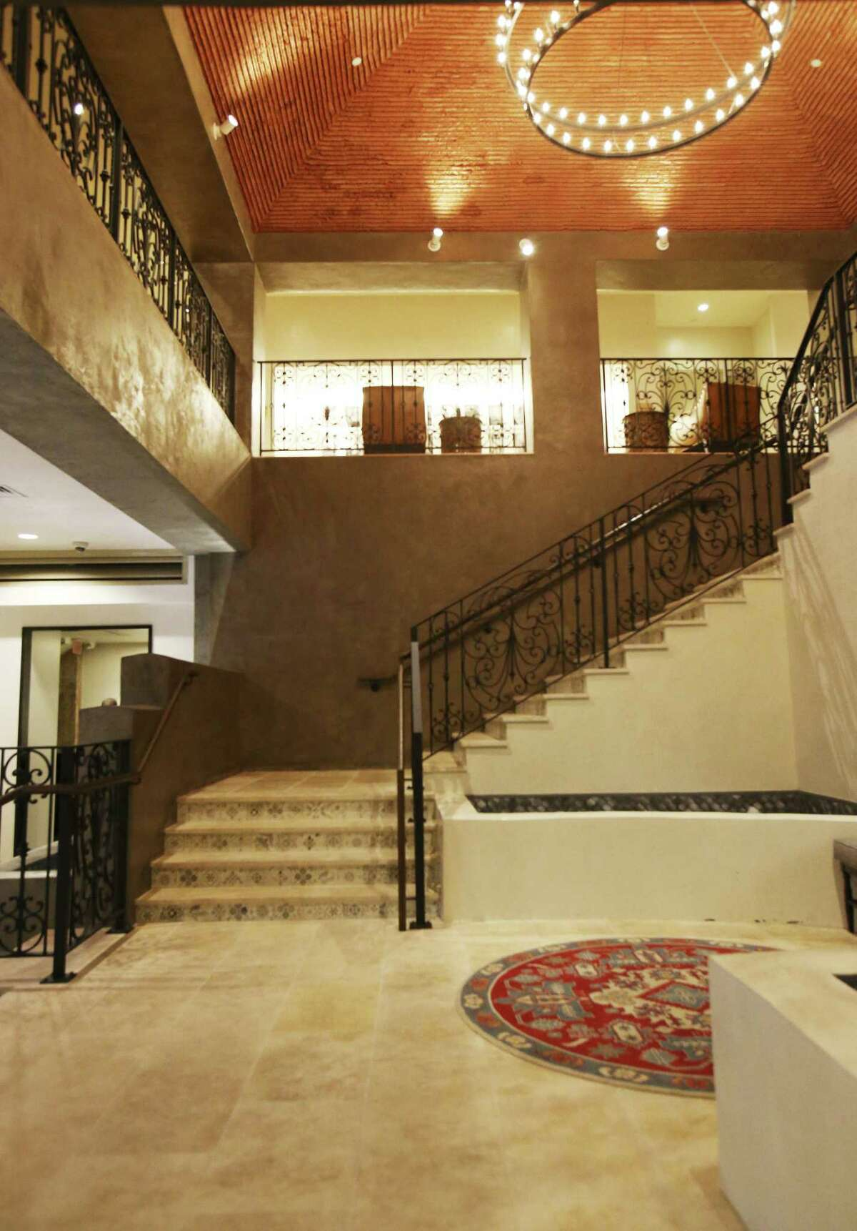 The Valencia foyer features a limestone staircase with a wrought iron railing, along with a custom chandelier and water feature.