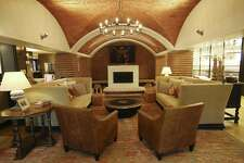 """The """"living room,"""" with custom couches and a fireplace where the old """"candle wall"""" stood, separates Naranja cafe and bar from Dorregos restaurant."""