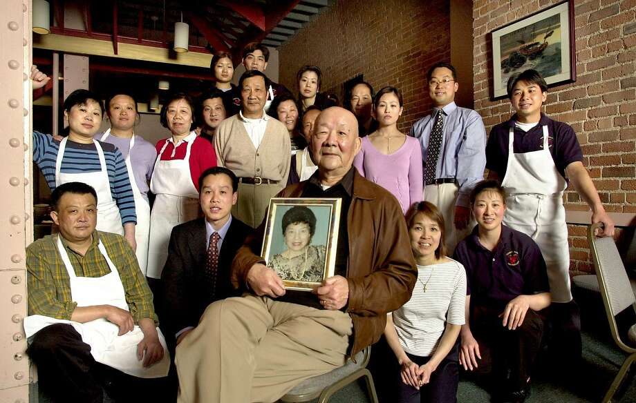 From 2004: Center sits Henry Chung, the patriarch of the Chung family. Henry holds a portrait of his late wife, Diana Chung, who was instrumental in his life and business. Surrounding Henry are 19 employees of the restaurant, most of them related to Henry. Photo: Katy Raddatz, SFC
