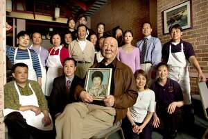 FAMILY102_rad.jpg  SHOWN:  Center sits Henry Chung, the patriarch of the Chung family, who has been running the Hunan restaurant since 1974. Henry holds a portrait of his late wife, Diana Chung, who was instrumental in his life and business. Surrounding Henry are 19 employees of the restaurant, most of them related to Henry.  The Chung family has been operating Hunan Restaurant since 1974.  An estimated 40 relatives work for the restaurant, making it a true family business.  We go to the Hunan at 110 Natoma St. in San Francisco to photograph the Grandfather, Henry Chung, with a gathering of relatives who work in the restaurant.   Katy Raddatz / The Chronicle