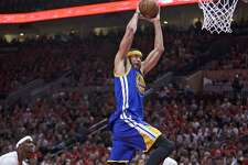Golden State Warriors center JaVale McGee, right, dunks over Portland Trail Blazers forward Noah Vonleh during the first half of Game 3 of an NBA basketball first-round playoff series Saturday, April 22, 2017, in Portland, Ore. (AP Photo/Craig Mitchelldyer)