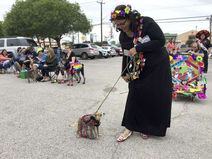 Elva Cope shows off her winning shoes, decorated by daughter Selena as race cars, with Bud the Chihuahua at Fiesta 4 Paws.