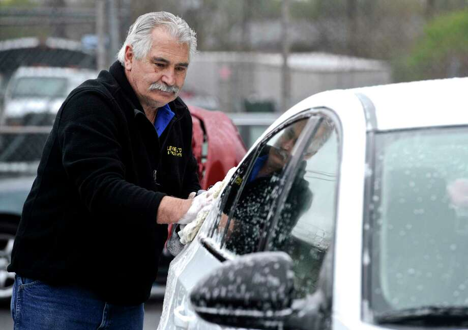 Mindo Freitas, one of the owners of Crossroads Auto Body, washes a car in the rain on Tuesday afternoon. Freitas was getting the car ready to be picked up. April 25, 2017, in Danbury, Conn. Photo: H John Voorhees III, Hearst Connecticut Media / The News-Times