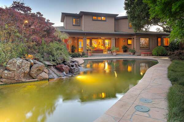 The backyard offers a solar-heated pool bordered by a stone patio.