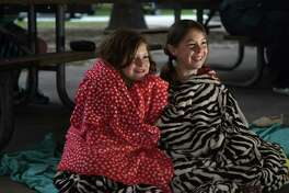 "Hadley Barcelona, 9, left, a 4th grader at Yeager Elem., and Ta'lana Holland, 9, a student at Talent Unbound, stay warm under their blankets as they watch an evening performance of Shakespeare in the Shade's ""All's Well That Ends Well"" on the pavilion stage at Burroughs Parks in Tomball on Arpil 22, 2017. ((Photo by Jerry Baker/Freelance)"