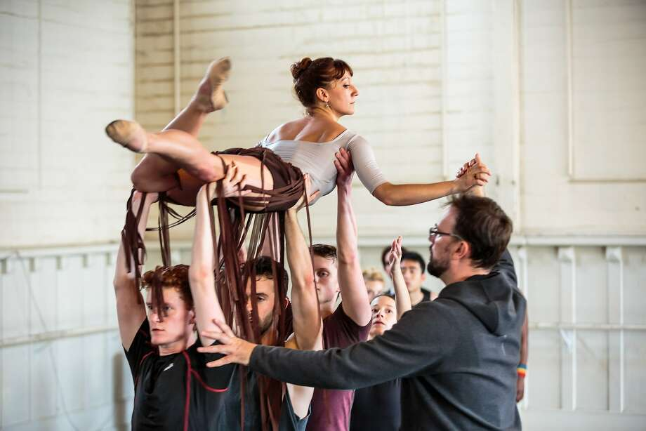 """Above:  Smuin dancers leap in a rehearsal of """"Be Here Now,"""" a world premiere tribute to the Summer of Love. At right: Smuin's Erica Chipp is lifted by fellow company members, overseen by choreo grapher Trey McIntyre. Photo: Chris Hardy"""