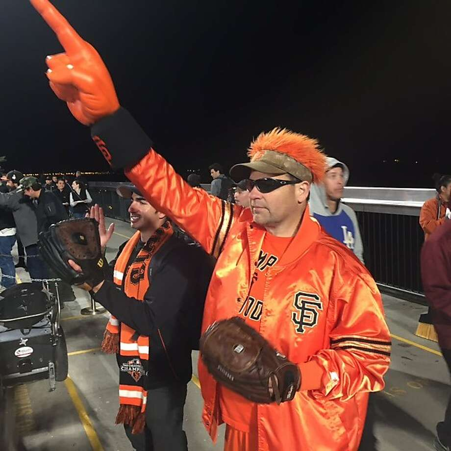 Giants fan Marc Roberts in his game pose before reaching for his cell phone to raise a rally flashlight Photo: Sam Whiting