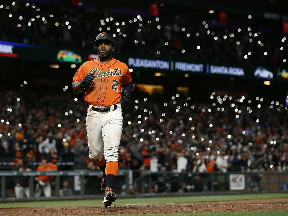 Giants outfielder Denard Span (2) scores on a Brandon Belt single as fans rally the team by holding up cell phones with the flashlight app turned on. Photo: Tony Avelar, Associated Press