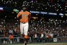 San Francisco Giants' Denard Span (2) scores a run on a single by Brandon Belt against the Colorado Rockies during the seventh inning of a baseball game, Friday, April 14, 2017, in San Francisco. Fans light up the stands with their phones. TheGiants won 8-2. (AP Photo/Tony Avelar)