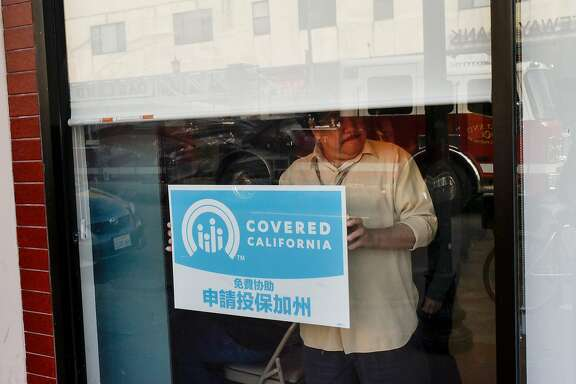 A sign for Covered California in the window of the Asian Health Services offices.�Despite Washington's repeal of the individual mandate, California has options for preserving its successful state-run insurance marketplace.